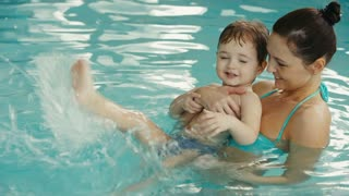 mother with her baby have fun in the pool