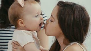 older sister kissing her baby sister
