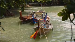 three wooden Asian boats anchored