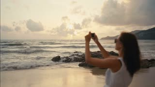 traveler woman taking pictures of beautiful sunset on smartphone