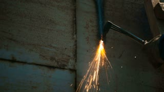 Worker cutting metal with acetylene torch