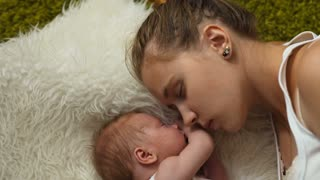 Young mom with his newborn baby girl top view