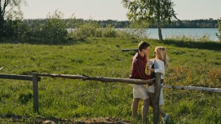 Young romantic couple standing on the river bank