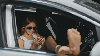 young woman in sunglasses resting in the car and Sending Messages
