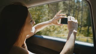 young woman takes pictures from the car window