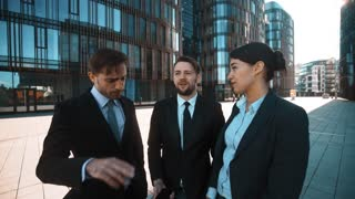 4k. POV. Big deal abstract attention calling. Interesting talking, smiling. Three Young successful attractive businessmen and businesswoman in deal suits give hand with mobile phone to You. Modern