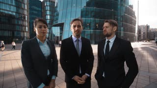 4k. POV. Three business people businessman and businesswoman loudly reproach negative discontent and reject Your opinion in formal suits outdoors. Teal orange sunrise. Wide. Business glass building bg