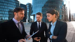 4k. POV. UHD. Your partner callegue calling. Team of business people give hand with mobile phone to You. Textpad. Businessman, businesswoman. Modern glass business centre district background. Teal