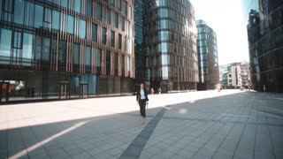 4k. POV. Young pretty sexy brownhair businesswoman in suit with documents on textpad walk to the camera and ask You for signature. She looks happy and smile a lot. Modern glossy building district