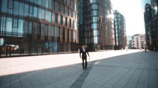 4k. POV. Young successful businessman in suit with documents on textpad and pen. Walk to the camera, handshake, and ask You for signature. Smile. Glass district bgsunset. Wide shooting. Teal and