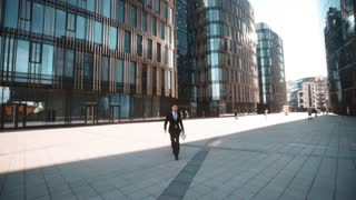 4k. POV. Young successful businessman in suit with documents on textpad walk to the camera, handshake and ask You for sign. Smile. Modern glass building district background at sunny afternoon. Wide