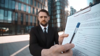 4k. POV. Young successful businessman with beard and mustache in suit with documents on textpad walk to the camera, handshake and ask You for sign seriously. Glass building district bg at sunset. Wide