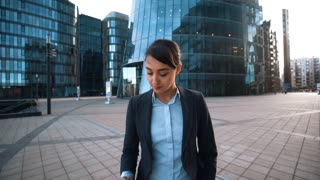 4k. POV. Your Family calling. Young successful brownhair caucasian attractive businesswoman in formal suit give mobile phone to You. Modern glass building bg. wide shot. Answer call concept. Sunrise