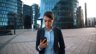 4k. POV. Your Parents attention calling. Young successful brownhair caucasian attractive businesswoman in formal suit give hand with mobile phone to You. Modern glass building bg. wide shot. Answer