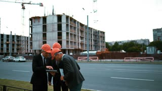 4k. UHD. Attractive successful business architect people in suits and helmets euphoric excult of finishing project. Digital Pad. Newly constructed building with crane and beams at bg. Teal and orange