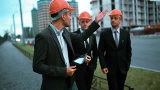 4k. UHD. Construction worker with tablet PC and business people in suit and protective helmets talking on site about new construction. Crane and beams at the background. Teal and orange steadicam