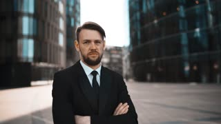 4K. UHD. Portrait of Young successful beard businessman in suit and tie disgusted with Your opinion. He looks mistrust with crossed hands. Head denial. Sunny morning teal and orange middle shot