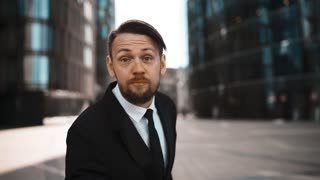 4k. UHD. Portrait Young successful angry Businessman swear and hating You. Formal suit and tie with beard and mustache. High bright emotion. Waving his arms, want to fight. Modern building district