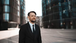 4k. UHD. Portrait Young successful Businessman approve Your opinion in formal suit and tie with beard and mustache. He gives thumb up and looks happy of praising You friendship and partners in