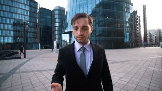 4K, UHD, POV, big deal ring. Young successful attractive Businessman in black suit and tie give hand with mobile phone to You. Glossy business centre building district at the bg. Please, answer call