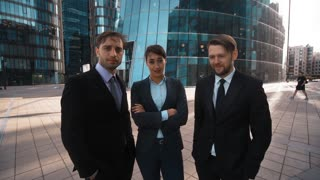 4k. UHD. POV. Three Young attractive businesspeople, Businessman and businesswoman, mock about Your opinion. Sarcasm, vitriol concept. Formal suit and tie. Business centre building modern district