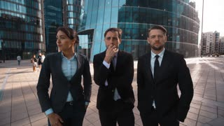 4k. UHD. POV. Three young attractive businesspeople discuss and born idea. Businesswoman and businessman. Lady, Gentleman. Male, female. Collegues, partners. Praise Glass modern building bg Teal