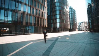 4k. UHD. POV Young successful serious attractive businessman in deal formal suit and tie with beard and mustache comes to You and shake your hand. Teal and orange wide shot. Sunset. Business centre