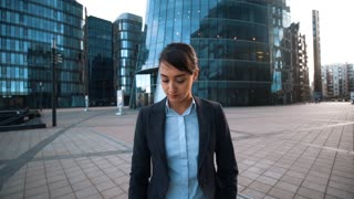 4k. UHD. POV. Your Friend calling. Young successful brownhair caucasian attractive businesswoman in formal suit give mobile phone to You. Modern glass business centre building bg. Wide shot. Teal