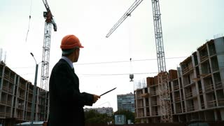 4K. UHD. Static shot of skyline and cranes, construction executive architect engineer consultant conduct and lead crane manipulation of beams of new urban development with caucasian construction
