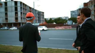 4k. UHD. Three attractive business people, 2 customers andarchitect in helmets with tabletPC and textpad calculation plan discussing about new constructed building at the background with crane and