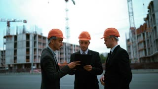 4k. UHD. Three customers: businessmen and architect sign document on text pad. They happy of a deal, smile and speaking. Orange helmets black suit and tie. Static middle shot with modern building
