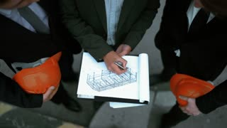 4k. UHD. Three successful businesspeople with orange helmets signing architecture documents outdoor near the new construction. Builders job concept