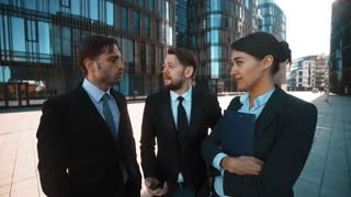 4k. UHD. Three young attractive succesful businesspeople ask You to answer call from Your Boss POV. Super wide shot. Sunny morning. Businessmen and businesswoman outdoor in modern fachion building