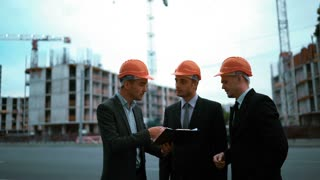 4k. Ultra HD. businessmen and architect sign document on textpad. They happy of good deal, smile and speak. Orange helmets black suit and tie. Static middle shot with modern building bg. Crane and