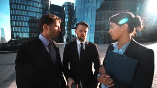 4k. Ultra HD. POV. Your customer calling. Team of business people give hand with mobile phone to You. Businesswoman and businessman. Textpad. Modern glass business centre bg. Teal orange sunrise
