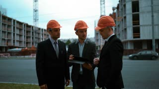 4K. ULTRA HD. Three youg successful Customers in orange helmets sign architect project on digital pad with newly constructed buildings at the bg. Handshake. Teal and orange middle shot