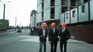 4k. Ultra HD. Three Young businessmans architect in suit and helmet discuss about newly constructed building with crane and beams at the background. TabletPC. Big project serious deal concept