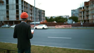 4k. Ultra HD. Unhappy customers discontent of constructor architect foreman worker with helmet in suit and outdoors on new house building blueprints with crane and beams at bg. Middle shot