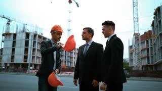 4k. Ultra HD. Young engineer architect giving successful businessmen in suits a helmets: come to work with me. Crane and beams building at the bg. Teal and orange static middle shot