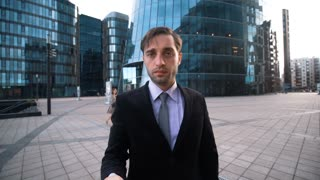 4k. UltraHD. POV. Child calling. Young successful attractive Businessman in black suit and tie give hand with mobile phone to You. Modern business centre district bg. Please, answer call concept. Teal