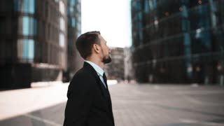 4k. UltraHD. POV. Portrait of angry Businessman swear and hate You. Formal suit and tie with beard and mustache. . Waving his arms, want to fight. Modern building glass district background. Teal