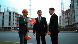 4k. UltraHD. Young engineer architect giving attractve businessmen in suits a helmets: come to work with me. Crane and beams construction at the bg. Teal and orange static middle shot