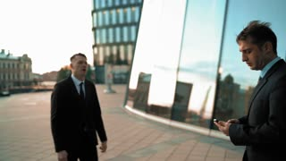 Angry Young businessman grabbing his colleague by the lapels of suite. He want to start fighting. Hard conversation and debate. Boss look at smart phone. Glass business centre building sunset at the