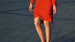 Attractive Young beautiful smiling businesswoman wearing High Heeled Shoes and bright red suit dress walking in the city with glass building bg. Look at camera. Steadicam Stabilized sunset slow motion