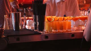 Barmen hand with shaker pouring cocktail