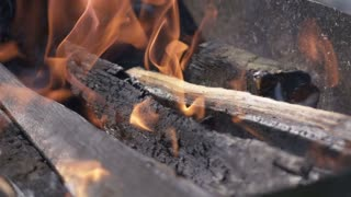 Big wooden log burning in the brazier with red flame in super slow motion. Macro high-speed camera view