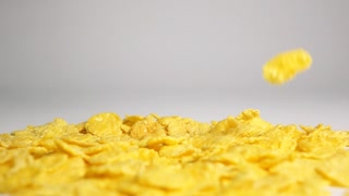 Crisp tasty cornflakes dropping down on dry white surface and bouncing and flying to different sides with high-speed-camera in slow motion mode. Gray background isolated