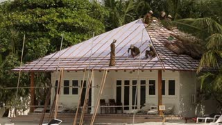 Few asian people build hay roof of white modern bungalow on tropical island near the beach
