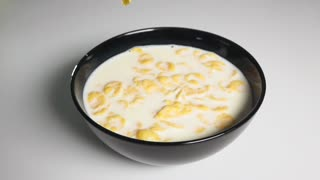 Filling crisp tasty corn flakes into fresh snow-white milk with stunning little explosive splashes on white background isolated. High-speed camera super slow motion shot