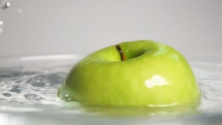 Fresh green apple swirling in the transparent water in super slow motion. Sony rx 10 ii isolated on gray background